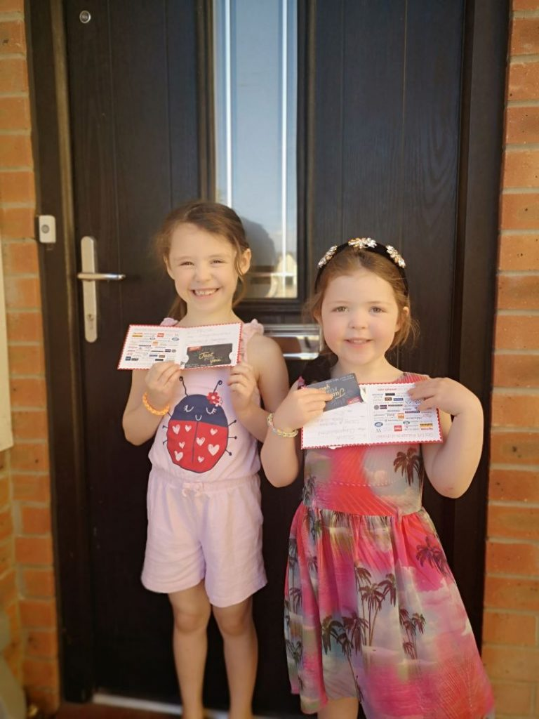 Two young girls standing in front of a brown front door, each holding their gift voucher prizes.