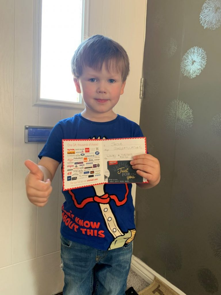 A young boy standing inside in front of a white front door, holding his winning gift voucher.