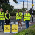 """Members of Lawley Community Speedwatch getting ready for their first speed monitoring operation on Dawley Road. The four people are standing next to each other on a footpath next to a pedestrian crossing, wearing high-visibility jackets. One of them is holding a speed gun, and two """"Community Speed Monitoring"""" signs are placed in front of them."""