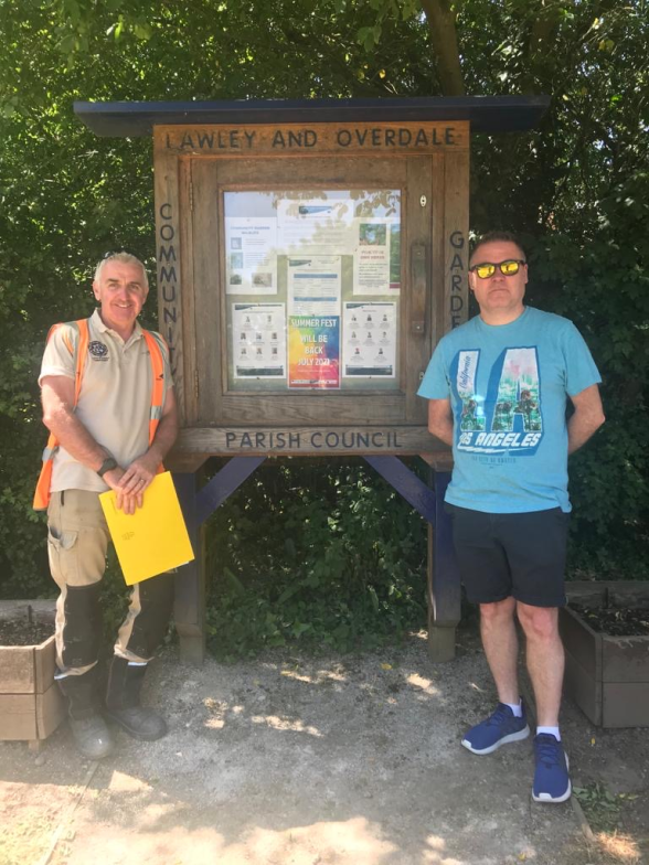 A photograph of two men standing either side of a large, wooden noticeboard, labelled 'Lawley and Overdale Parish Council Community Garden'. A series of posters are on display beneath a glass panel in the centre.