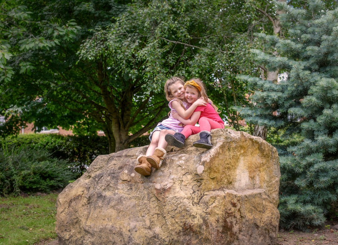 A photograph of two young children sitting on top of a large rock, hugging, against a backdrop of various trees.