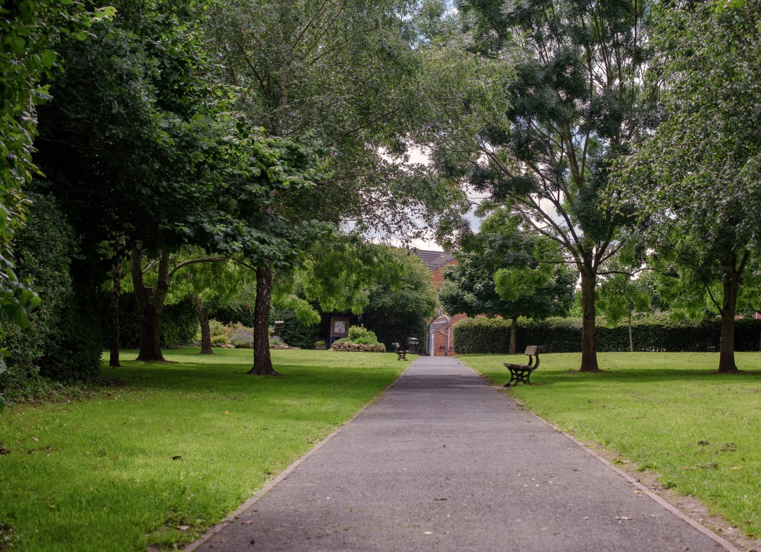 A long, straight footpath flanked by trees, with a bench midway along.