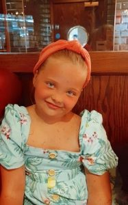 A photograph of Sienna, a little girl suffering from Landau Kleffner Syndrome, pictured sitting in a restaurant, smiling in a blue dress with a red headband holding back her hair.