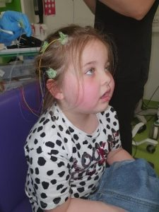 A photograph of Sienna, a little girl suffering from Landau Kleffner Syndrome, pictured in a hospital bed.