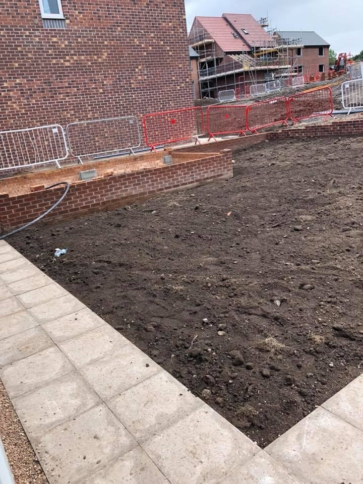 A photograph of a garden under construction, with a newly-laid, pale grey flagstone path in the foreground, which corners around some bare soil in the background.