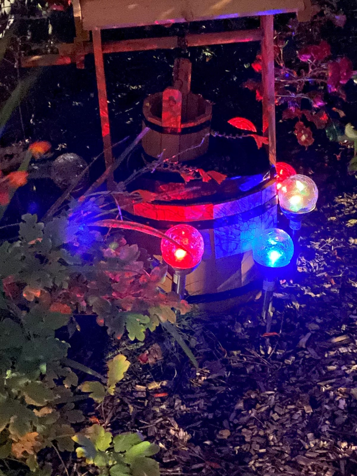 A photograph of a miniature, novelty wooden well sitting on a barked area, with blue and red lights and assorted plants around it.