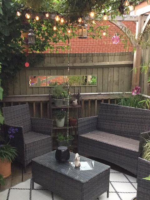 A photograph of a garden, with a wicker chair, wicker bench, and wicker coffee table on wooden decking, with strings of lightbulbs overhead, potted plants dotted around the furniture, and a fence with some plants growing up it in the background.