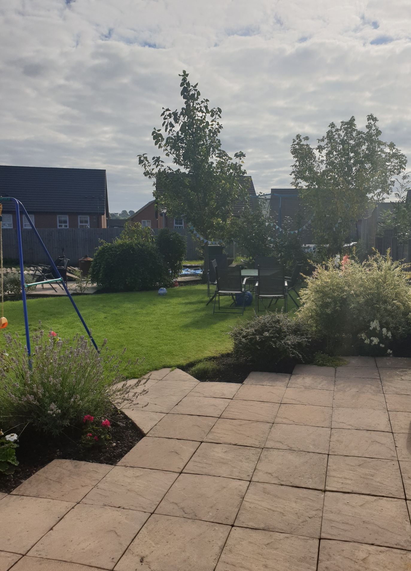 A photograph of a back garden, with a paved area surrounded by bushes and plants in the foreground, and a lawn in the background. A child's swing can be seen to the left.