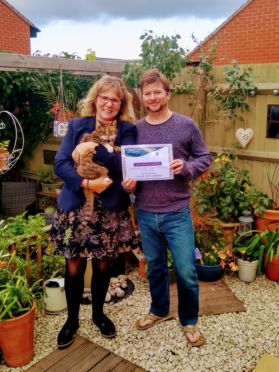 A photograph of Lorraine Rownes and her husband, standing beside the trellis in their garden holding their Best Garden Competition certificate together.