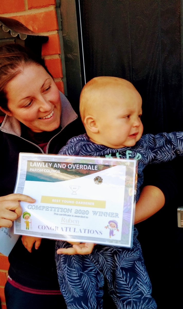 A photograph of Ruben, being held by his mother, along with his winning certificate.