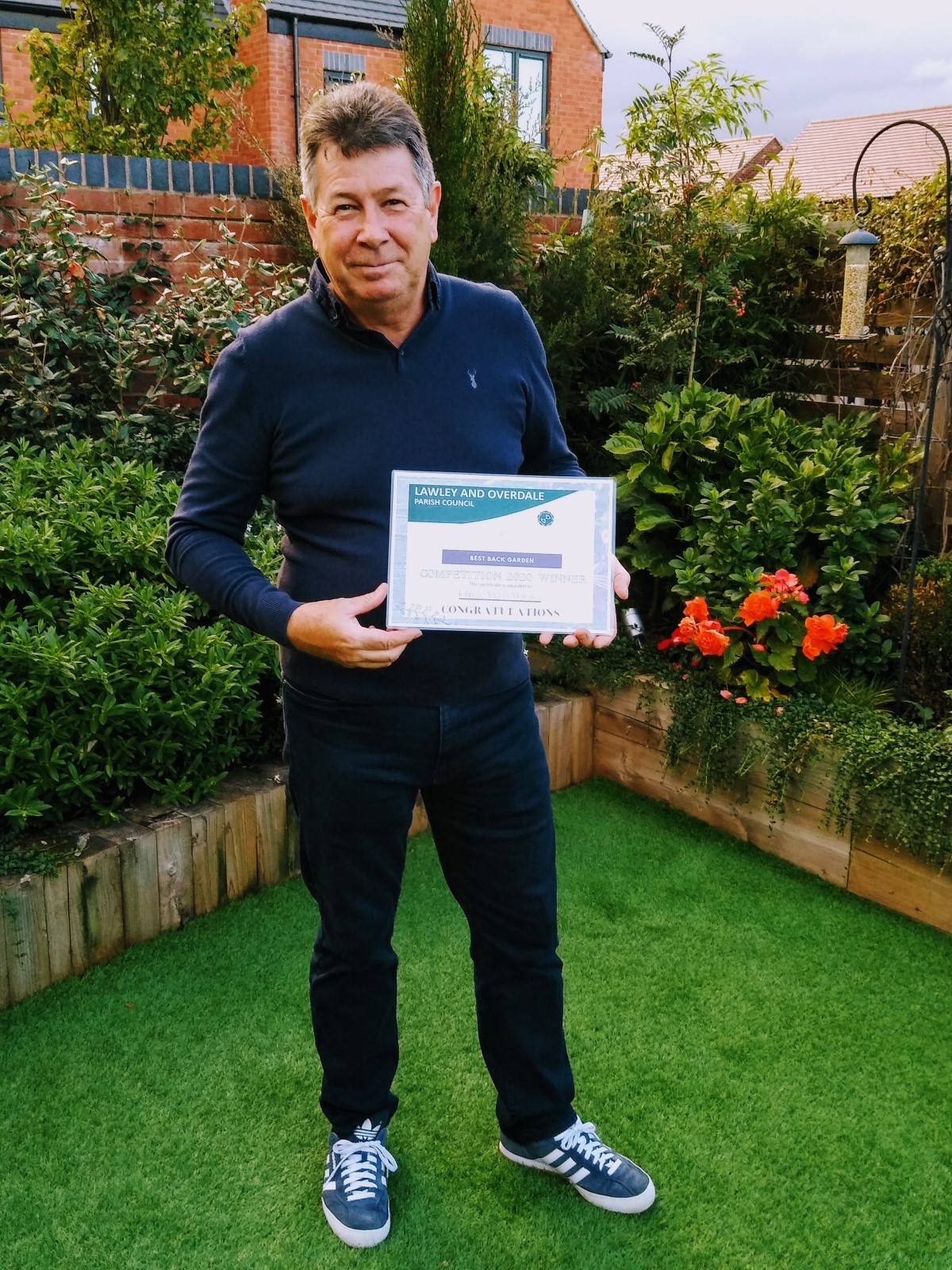 John, pictured in his garden with his prize for winning the Best Back Garden category