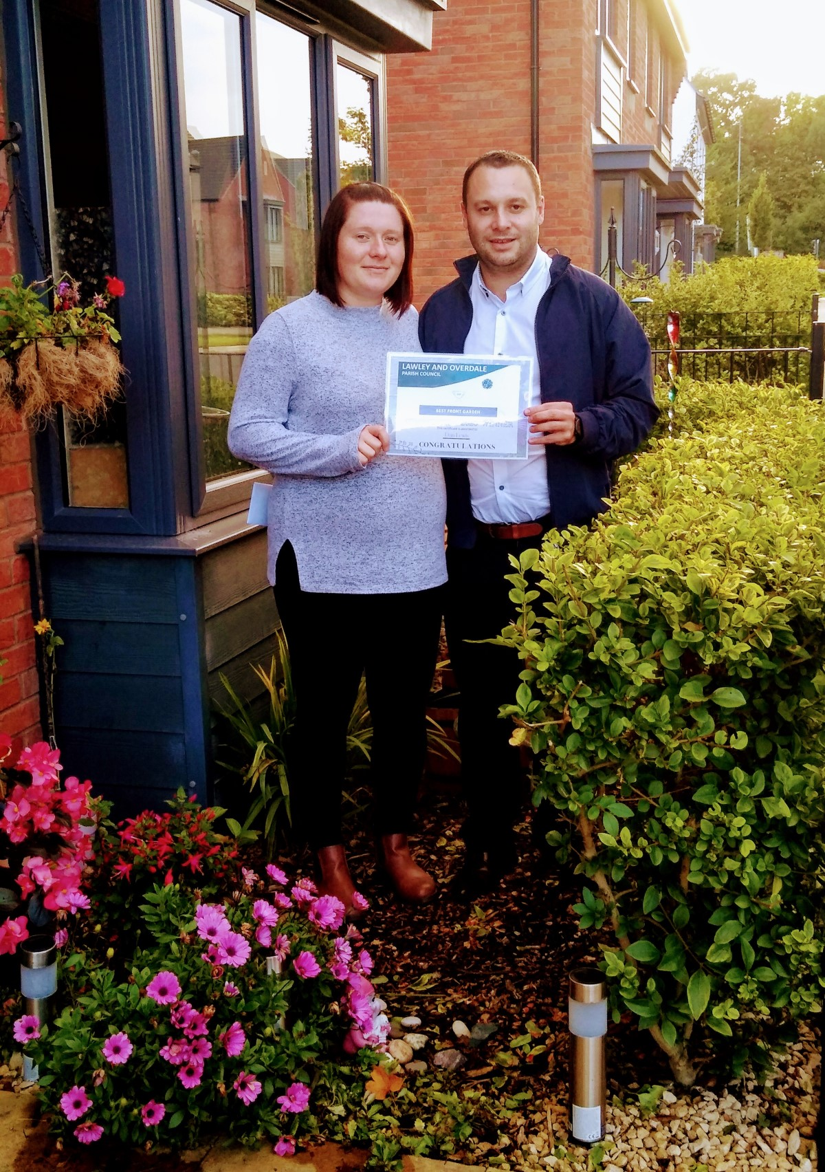 A photograph of a man and a woman standing next to each other in their front garden, next to a window and surrounded by plants. They are holding their Best Garden Competition certificate together.