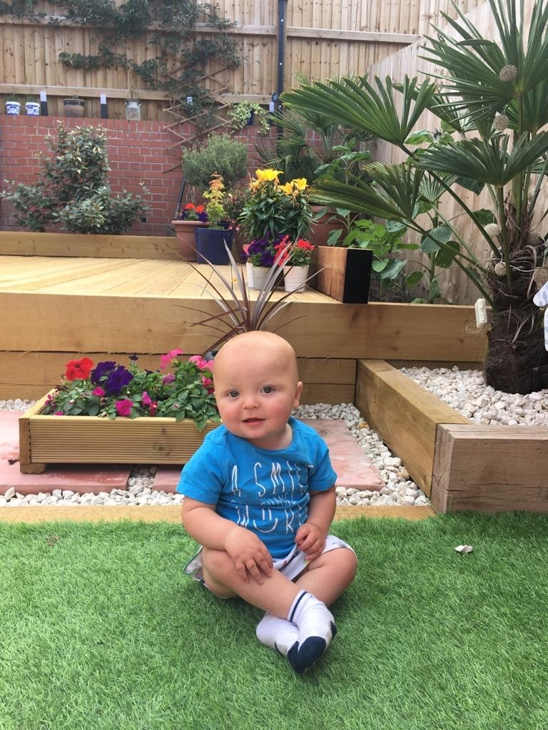 A photograph of Ruben, a baby boy wearing a blue T-shirt and smiling at the camera, sitting on the lawn in front of a series of potted flowers and a small palm plant.