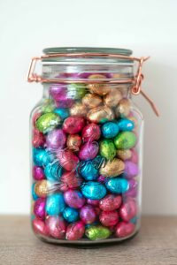 A photograph of a clear glass jar, filled to the brim with small, foil-wrapped, multi-coloured chocolate eggs.