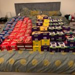 A large quantity of various boxed Easter eggs laid out on a bed.