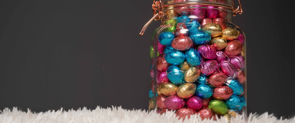 A cutout photograph of a jar full of small, foil-wrapped, colourful chocolate eggs, resting on a fur surface against a black background.