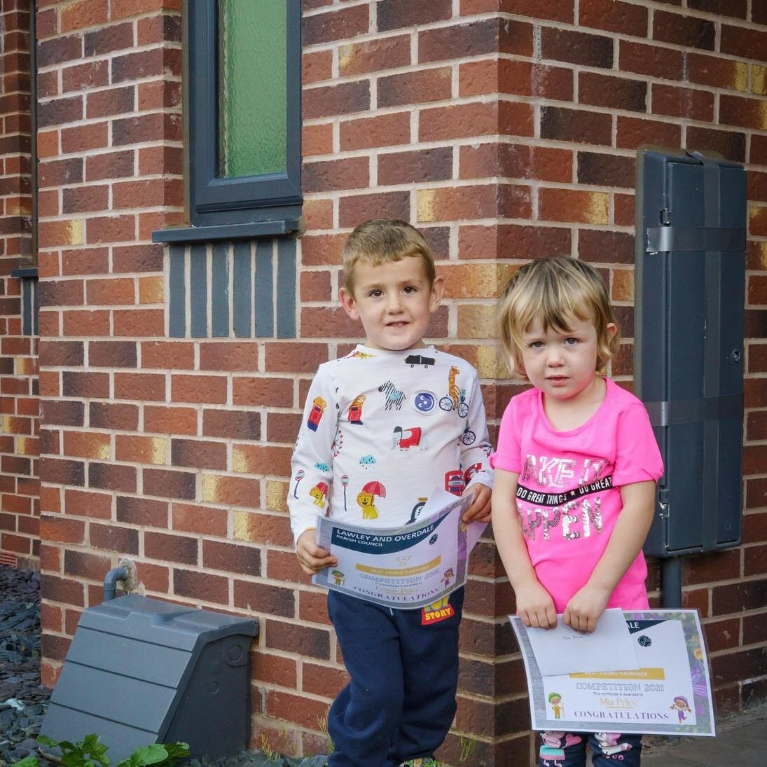 Two children standing outside of a house, with one of them holding a certificate.
