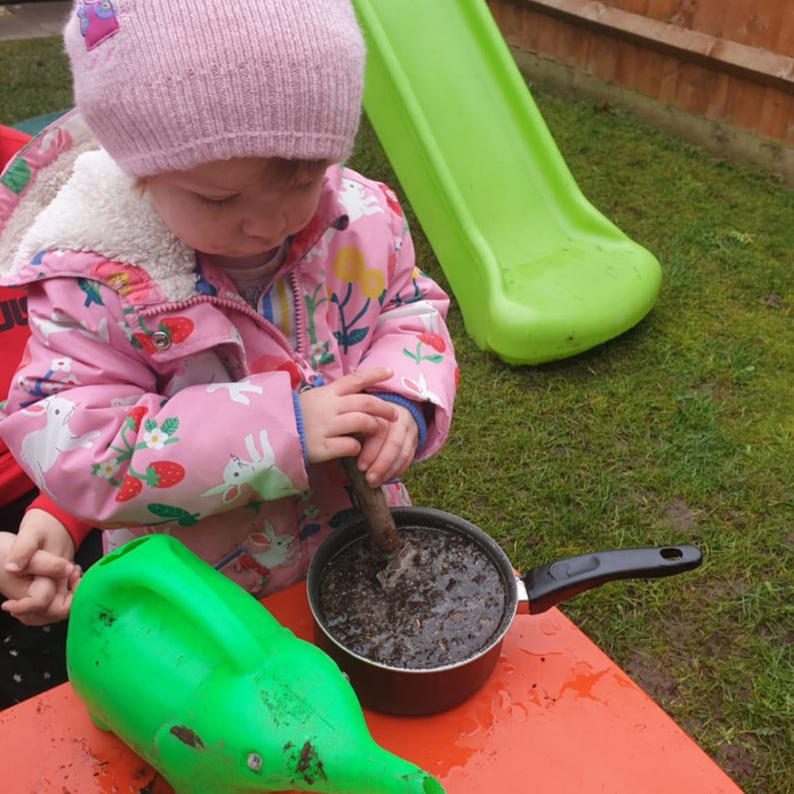 A child in pink, mushing up some mud in a pan on a red child's table.