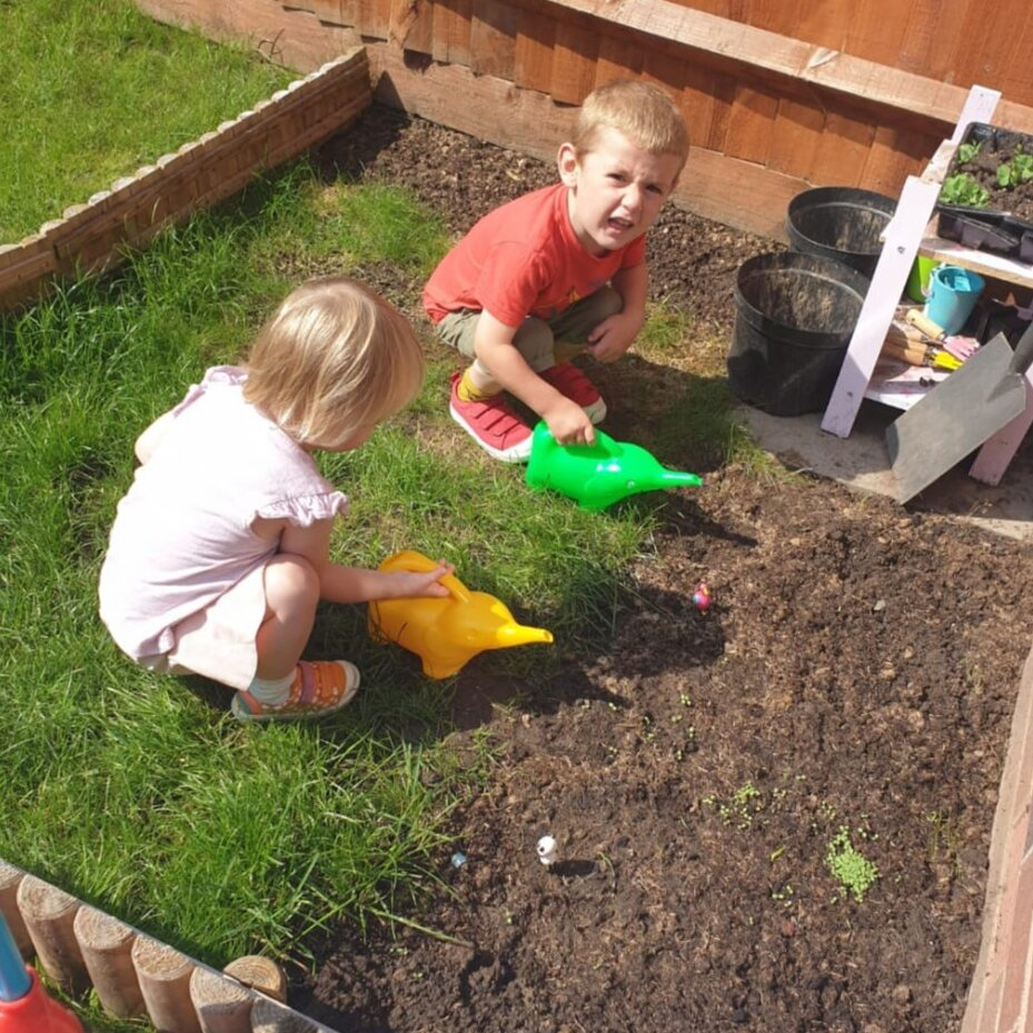 Two children crouching down over some soil, each with a watering can.