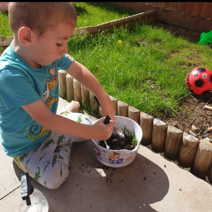 A child mixing some soil in a pot.