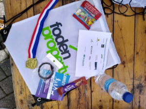 A table with the contents of the goody bags laid on it - a Foden Property bag, a bottle of water, a Cadbury Brunch Bar, a watch in a bag, a gold 'Fun Run' medal, and a small bag of Haribo.