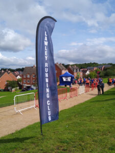 A long, tall, blue flag with 'Lawley Running Club' written down it.