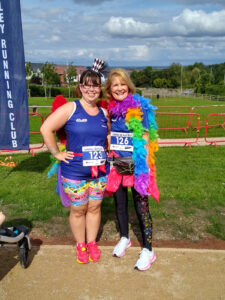Two women, both in running gear, with one wearing a top hat and wings, and the other a colourful feather boa, both smiling for the camera.