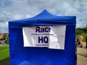 A close-up of a blue tent with a 'Race HQ' sign on the side.