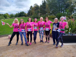 Eight women in pink 'Lawley Walkers' T-shirts, all standing with interlocked arms and smiling for the camera.