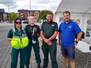 Three paramedics standing next to a man in a Lawley Running Club T-shirt, all smiling for the camera.