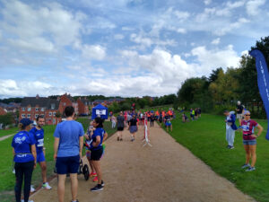 A photograph showing a long gravel path, with runners all congregating along it.