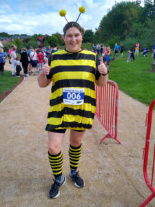 A woman in a bumblebee outfit, with her thumbs up and smiling for the camera.