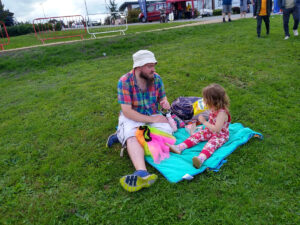 A man and a child sitting on a blanket on the grass, eating a picnic.