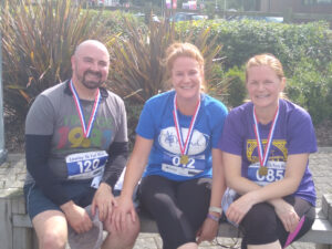 Three people in running clothes sitting on a bench and smiling for the camera.