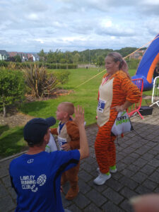 A woman in a 'tiger' outfit standing next to a small child in a tiger outfit.
