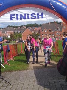 Three people walking across the finish line.