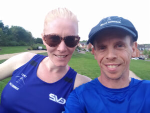 Two people in running gear smiling for the camera.