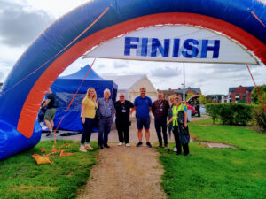 Seven people standing beneath an inflatable, blue and red 'finish' sign.