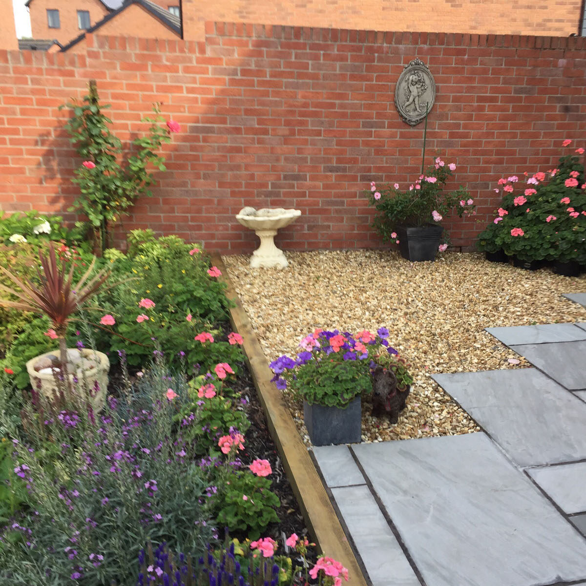 A photo of a brick-walled garden, looking across a patio and gravel area surrounded by flowerbeds and bushes.