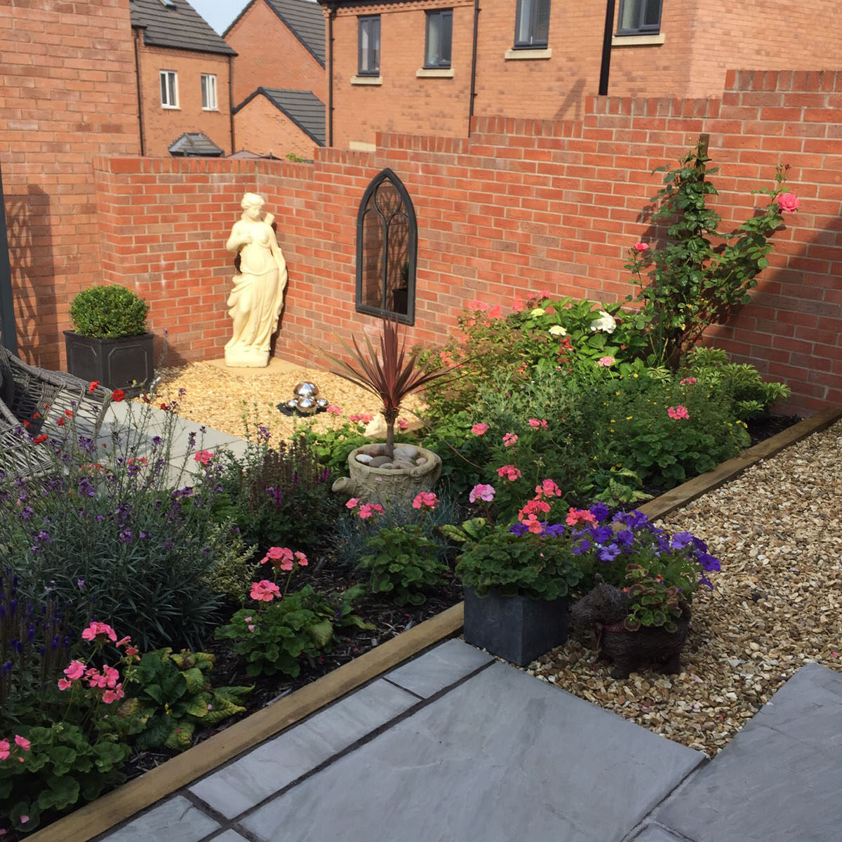 A photo of a brick-walled garden, looking down past flower beds with a statue in the corner.