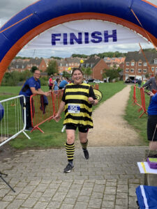 A woman in a bumblebee outfit jogs across the finish line.