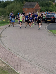 A long, close-knit crowd of runners, running down a red brick road past a parked car.