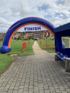 A photo of the inflatable, blue and red finish line, with a gravel path stretching off in the distance.