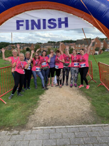 A line of women, mostly wearing pink 'Lawley Walkers' T-shirts, stand beneath the finish line waving.