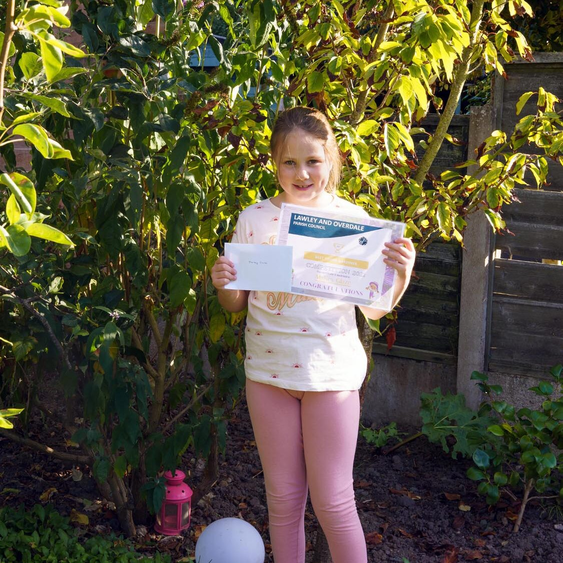 A young girl standing in front of some trees, holding a certificate.