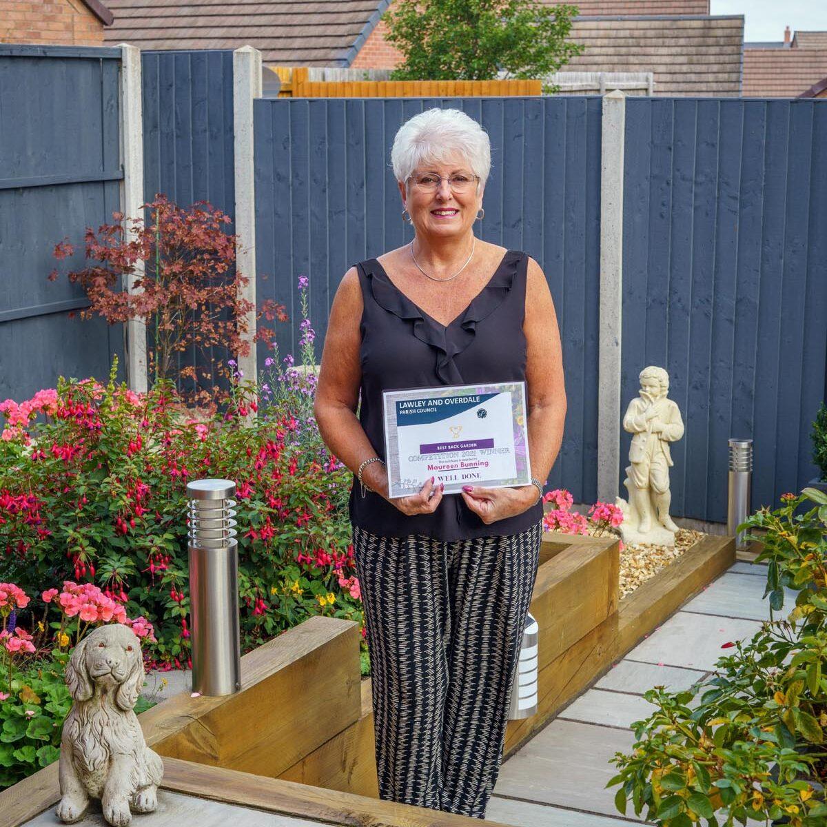 Maureen Bunning standing in her garden, holding a certificate.