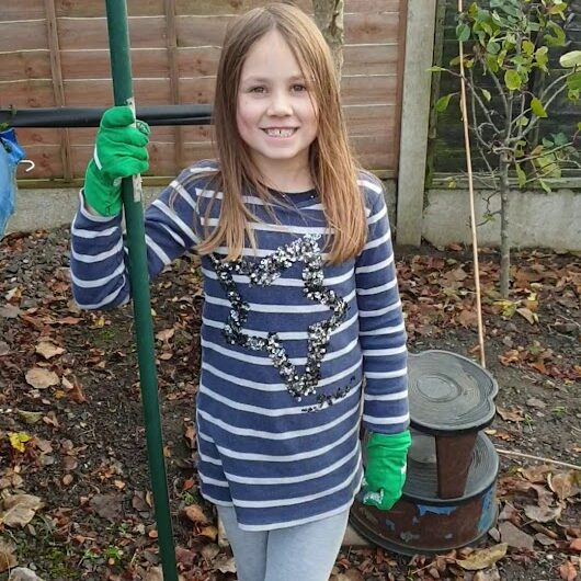A young girl in garden gloves, standing in front of some saplings and holding a hoe.
