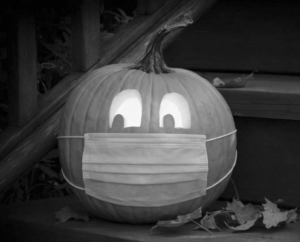 A Jack-o'-Lantern wearing a face mask.